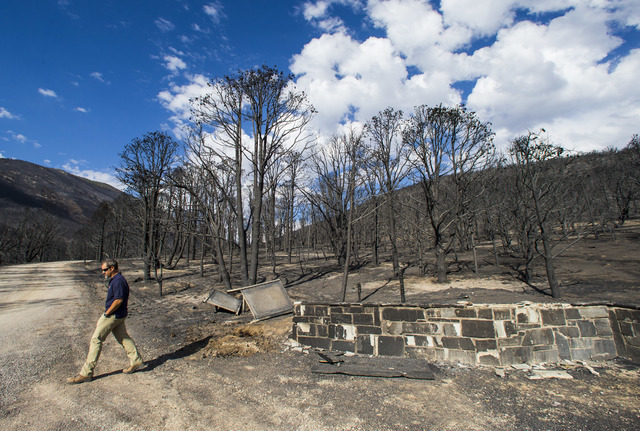 Ben Roberts, chief of natural resources at Great Basin National Park, walks by burnt out signs damaged by the Strawberry Fire at Great Basin National Park on Thursday, Aug. 25, 2016. Chase Stevens ...