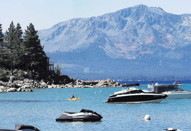 FILE -- In this Aug. 24, 2015 file photo, a kayaker paddles along Zephyr Cove, the sight of the 19th Annual Lake Tahoe Summit Monday, Aug. 24, 2015.  The summit brought together lawmakers,  includ ...
