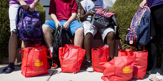 Teenagers sit outside of Project 150, a local non-profit, with their bags of clothing items and shoes provided by the non profit Saturday, Aug. 20, 2016, in Las Vegas. (Elizabeth Page Brumley/Las  ...