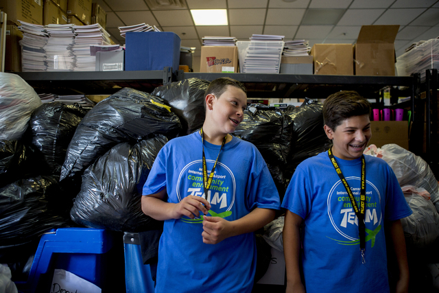 Project 150 volunteers Noah Blut, 13, left, and Damon Ayla, 13, stands near donated goods during free teen shopping day at Project 150, a local non-profit, Saturday, Aug. 20, 2016, in Las Vegas. ( ...