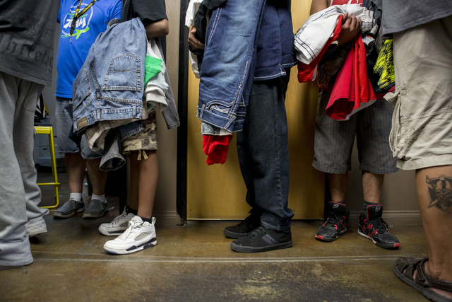 Teenagers stand in line with their chosen clothing options  in Project 150, a local non-profit, during free teen shopping day put on by the non-profit Saturday, Aug. 20, 2016, in Las Vegas. (Eliza ...