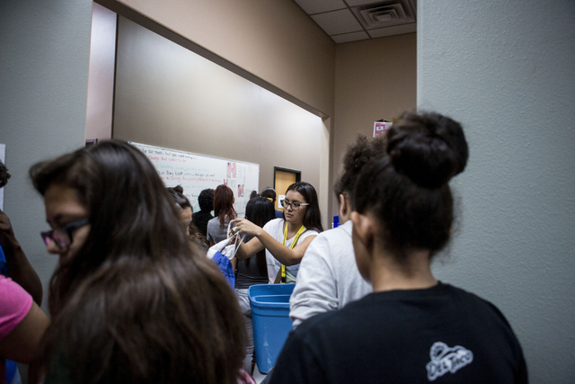 Sunrise hospital volunteer Leilany Guerrero, 17, center, takes off hangers for clothes chosen by teenagers during free teen shopping day at  Project 150, a local non-profit, Saturday, Aug. 20, 201 ...