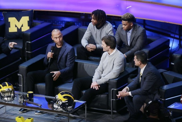 Derek Jeter, left, talks with former Michigan school quarterback Tom Brady and Michigan football coach Jim Harbaugh, right, as new recruits Kingston Davis, top right, and Ahmir Mitchell listen in, ...