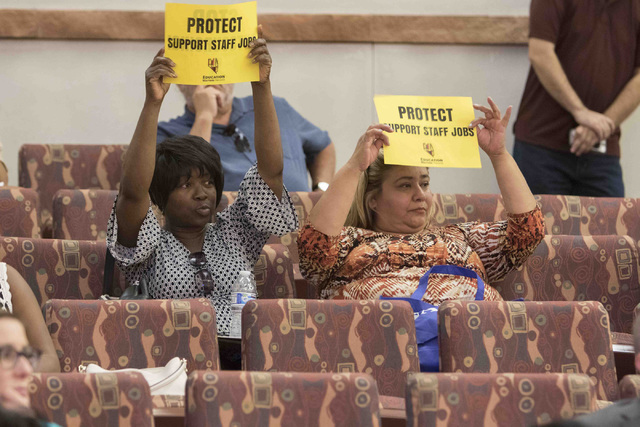 Proponents of the Clark County School District support staff hold up their signs during a town hall meeting at the Clark County Government Center in downtown Las Vegas on Tuesday, Aug. 9, 2016. Ri ...