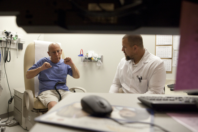 Navy veteran Ray Burroughs, right and Dr. Bryan Werner of the North Las Vegas VA Medical Center consults with Dr. John Frazee, a neurosurgeon in Los Angeles, Calif. using telemedicine technology o ...