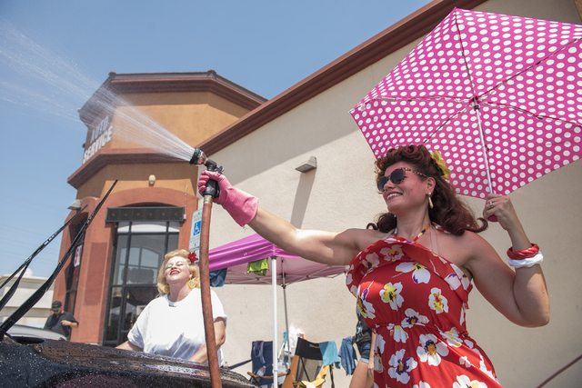 Pinups for Patriots girl Sinthia Sterling, left, hoses down a car in over 100 degree weather during their car wash event to raise money to send care packages to the troops at Lost in the 50's Auto ...