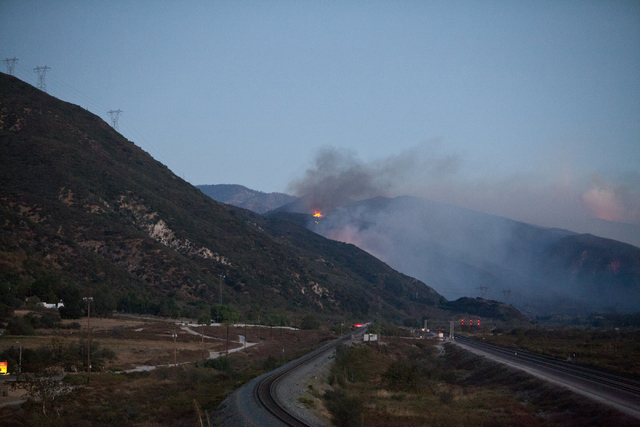 The Blue Cut Fire burns west of Interstate 15 at the north junction with Interstate 215 on Wednesday, Aug. 17, 2016, in San Bernardino County, Calif. I-15 remains closed in this area. (Loren Towns ...