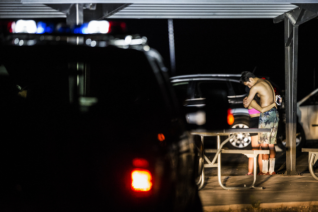 Friends of the deceased hiker console each other at a helicopter pad at the overlook at Red Rock Canyon National Conservation Area on Thursday, Aug. 25, 2016, in Las Vegas.  (Benjamin Hager/Las Ve ...