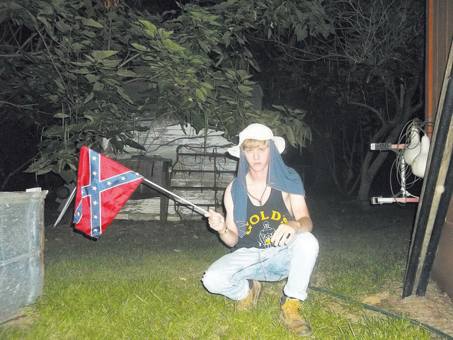 A handout photograph posted to a website with a racist manifesto shows Dylann Roof, the suspect in Wednesday's Charleston church massacre, posing with a Confederate flag in an unknown location. (H ...