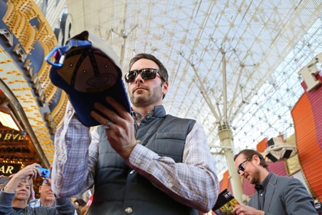 NASCAR drivers Jimmie Johnson, front, and Kurt Busch, back, sign autographs during a NASCAR FanFest event at Fremont Street Experience Wednesday, Dec. 2, 2015, in Las Vegas. (Ronda Churchill/Las V ...