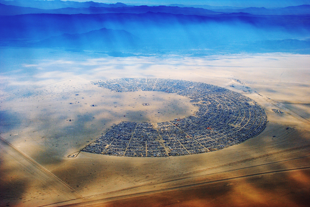 """Burning Man unfolds on the Black Rock Desert playa in this aerial photo by Will Roger Peterson, cofounder the annual festival, from the """"Home Means Nevada"""" exhibit now on display ..."""