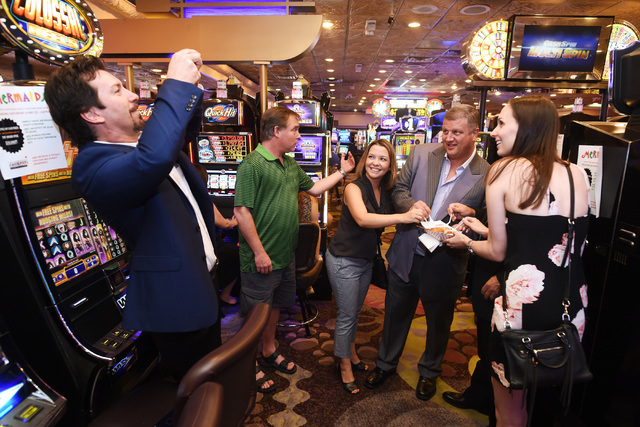 From left, Lorena Amaya, co-owner and CEO of Desert Rock Enterprises Derek Stevens and Sarah Cass have their photo taken digging into one of Mermaids Casino's deep-fried Twinkies Saturday, June 25 ...