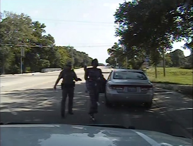 Texas state trooper Brian Encinia points a Taser as he orders Sandra Bland out of her vehicle, in this still image captured from the police dash camera video from the traffic stop of Bland's vehic ...