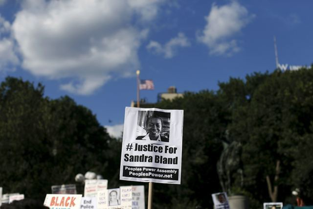 Demonstrators hold signs of Sandra Bland who was found hanged in her Texas jail cell after being taken into custody following a traffic stop, during a rally against police violence in New York on  ...