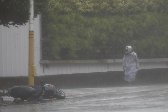 A motorcyclist takes cover from strong winds as Typhoon Megi hits Hualien, eastern Taiwan, September 27, 2016. (Tyrone Siu/Reuters)