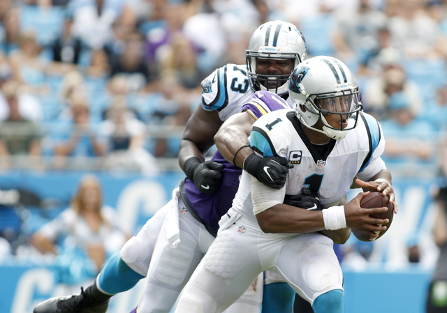 Minnesota Vikings' Everson Griffen (97) gets a good hold on Carolina Panthers' Cam Newton (1) for a sack as Michael Oher (73) follows the play during the second half of an NFL football game in Cha ...