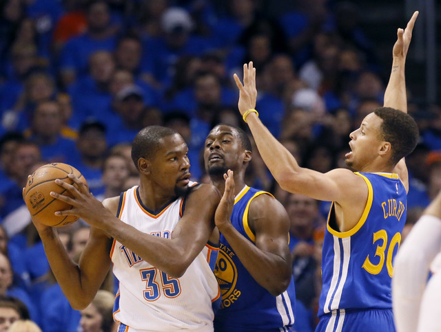 Oklahoma City Thunder forward Kevin Durant (35) is guarded by Golden State Warriors forward Harrison Barnes (40) and guard Stephen Curry (30) during the first quarter in Game 3 of the NBA basketba ...