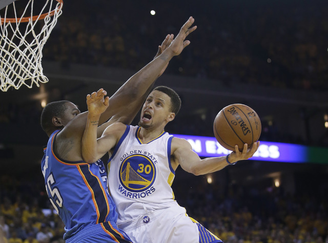Golden State Warriors' Stephen Curry (30) drives to the basket as Oklahoma City Thunder's Kevin Durant defends during the second half in Game 5 of the NBA basketball Western Conference finals Thur ...