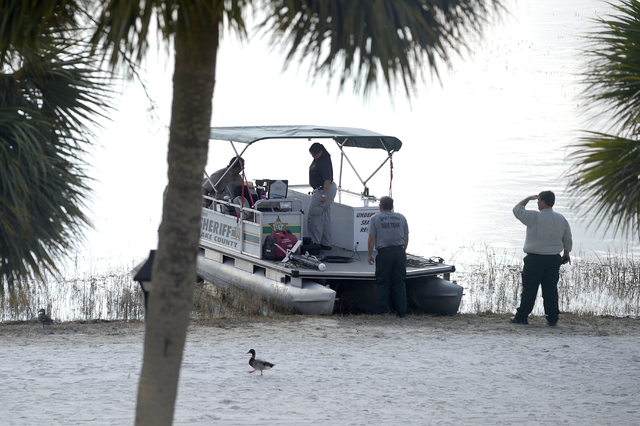 In this June 15, 2016 file photo, law enforcement officials search the Seven Seas Lagoon outside the Grand Floridian Resort & Spa in Lake Buena Vista, Fla., after Lane Graves, a two-year-old t ...