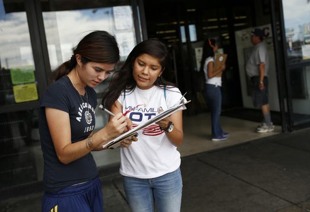Fabiola Vejar, right, registers Stephanie Cardenas to vote in front of a Latino supermarket in Las Vegas on June 9, 2016. (John Locher/Associated Press)