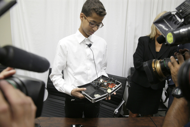 Ahmed Mohamed shows the clock he built in a school pencil box to reporters after a news conference in Dallas, Monday, Aug. 8, 2016. The family of Ahmed Mohamed, who was arrested after bringing the ...