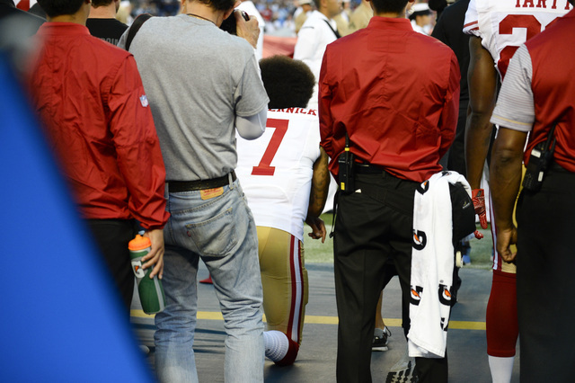 San Francisco 49ers quarterback Colin Kaepernick, middle, kneels during the national anthem before the team's NFL preseason football game against the San Diego Chargers, Thursday, Sept. 1, 2016, i ...