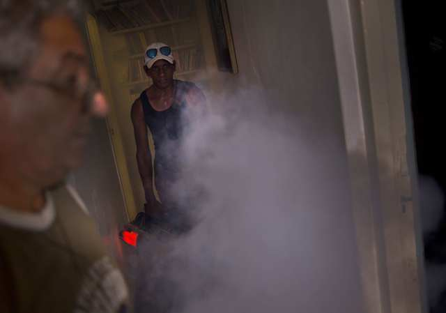 In this Aug. 26, 2016 photo, a government fumigator sprays a home for mosquitos in Havana, Cuba. (Ramon Espinosa/AP)