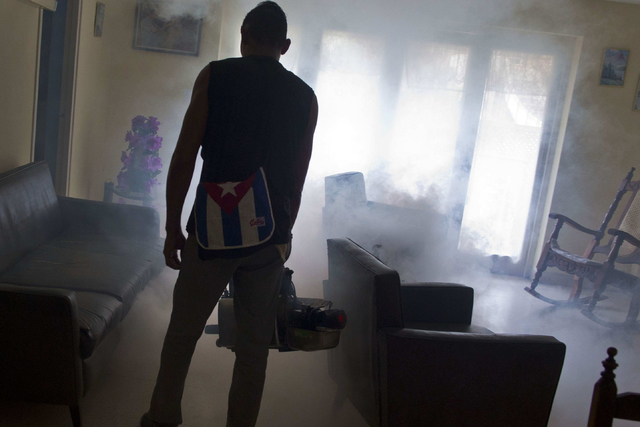 A government fumigator sprays a home for mosquitos in Havana, Cuba, on Friday, Aug. 26, 2016. Cuba's massive bureaucracy has been deployed with remarkable success in the battle against Zika. (Ramo ...