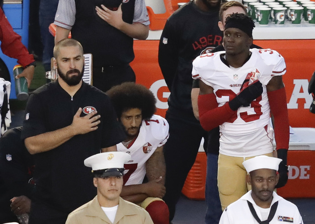 In this Thursday, Sept. 1, 2016 file photo, San Francisco 49ers quarterback Colin Kaepernick, middle, kneels during the national anthem before the team's NFL preseason football game against the Sa ...
