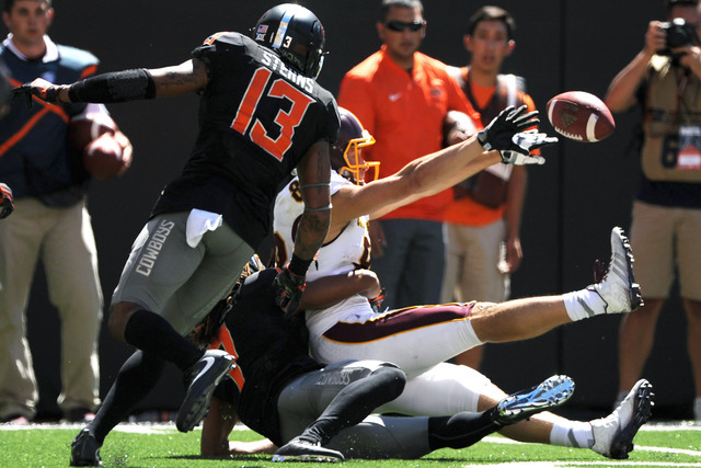 Oklahoma State safety Jordan Sterns, left, watches as Central Michigan wide receiver Jesse Kroll, right, being tackled by Oklahoma State corner back Ramon Richards, bottom, tosses the ball back to ...