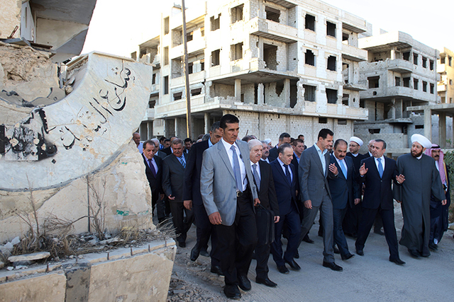 Syrian President Bashar Assad, center, walks on a street with officials after performing the morning Eid al-Adha prayers in Daraya, a blockaded Damascus suburb, Syria, Monday, Sept. 12, 2016. Syri ...