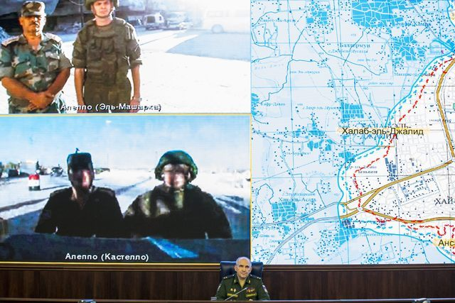 Lt.-Gen. Sergei Rudskoi, center, of the Russian Military General Staff listens to Russian and Syrian officers during a video call, as a Syrian army facility is displayed on screen, at a Russian De ...