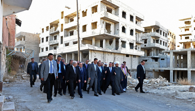 In this photo released by the Syrian official news agency SANA, Syrian President Bashar Assad, center, walks on a street with officials after performing the morning Eid al-Adha prayers in Daraya,  ...