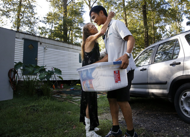 David Phung, who rescued Hailey Brouillette and her dog Sassy from her sinking car in recent floodwaters, hugs her as he gives her a box of household supplies, as they reunite for the first time.  ...