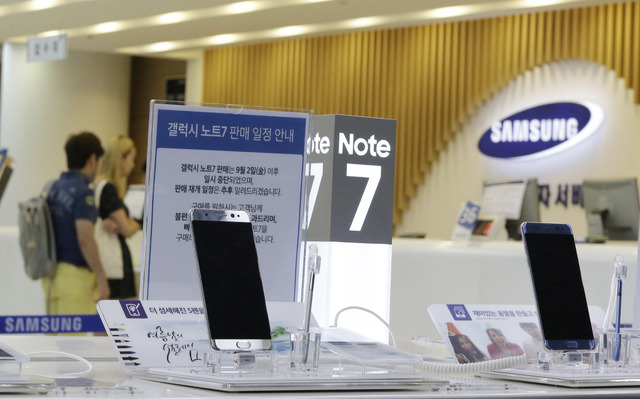 FILE - In this Sunday, Sept. 11, 2016 file photo, customers wait for recall of their Samsung Electronics Galaxy Note 7 smartphones as powered-off Galaxy Note 7 smartphones are displayed at the com ...