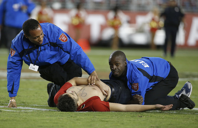 FILE - In this Sept. 12, 2016, file photo, a fan is tackled by security officers during the second half of an NFL football game between the San Francisco 49ers and the Los Angeles Rams in Santa Cl ...