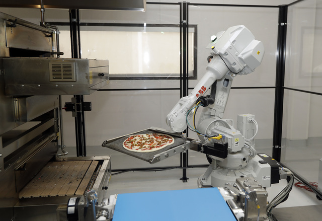 A robot places a pizza into an oven at Zume Pizza in Mountain View, California, in late August. The startup, which began delivery in April, is using intelligent machines to grab a slice of the mul ...