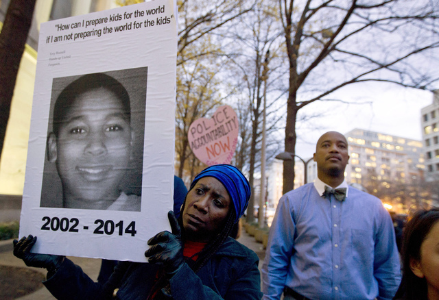 In a Monday, Dec. 1, 2014 file photo, Tomiko Shine holds up a picture of Tamir Rice during a protest in Washington, D.C. The gazebo where the 12-year-old boy, Rice, was fatally shot by a Cleveland ...