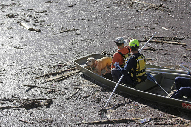 Searchers comb through mud and debris for the remaining victims of a flash flood in Hildale, Utah, Sept. 17, 2015. Community members gathered Wednesday night, Sept. 14, 2016, for a memorial servic ...