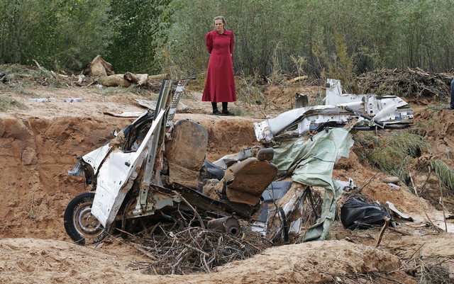 Awoman looks at a damaged vehicle swept away during a flash flood in Hildale, Utah, Sept. 15, 2015. Community members gathered Wednesday night, Sept. 14, 2016, for a memorial service.  (Rick Bowme ...