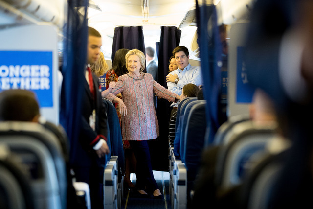 Democratic presidential candidate Hillary Clinton smiles as she speaks to aids on her campaign plane, in White Plains, N.Y., Thursday, Sept. 15, 2016, before traveling to Greensboro, N.C. for a ra ...