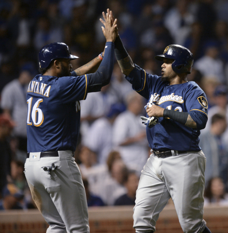 Milwaukee Brewers' Martin Maldonado (12) celebrates with teammate Domingo Santana (16) after both scored on a two-run double hit by Scooter Gennett during the seventh inning of a baseball game aga ...