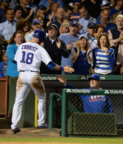 Chicago Cubs' Ben Zobrist (18) celebrates with manager Joe Maddon, right, after scoring during the seventh inning of a baseball game against the Milwaukee Brewers on Thursday, Sept. 15, 2016, in C ...