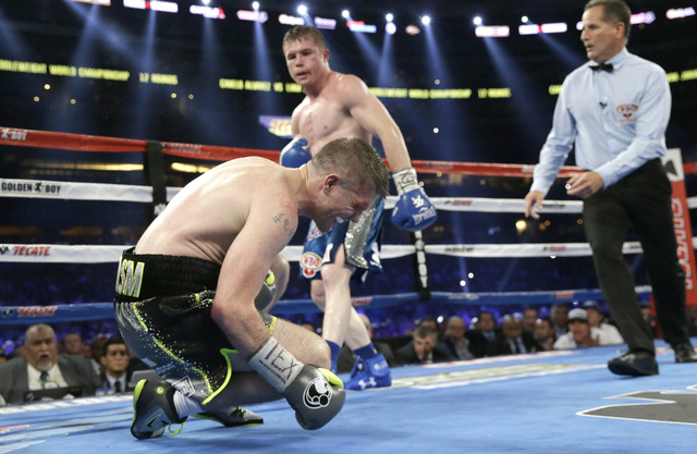 Liam Smith, left, falls to the mat after taking a body shot and being knocked out buy Canelo Alvarez fight during the ninth round of the WBO Junior Middleweight Championship boxing match at the st ...