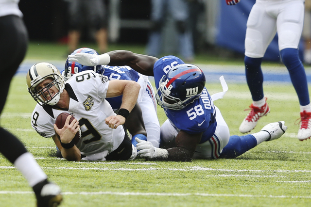 New Orleans Saints quarterback Drew Brees (9) is forced to the ground by New York Giants' Owa Odighizuwa (58) and Jason Pierre-Paul (90) after being tripped up by Leon Hall (25) for a sack during  ...