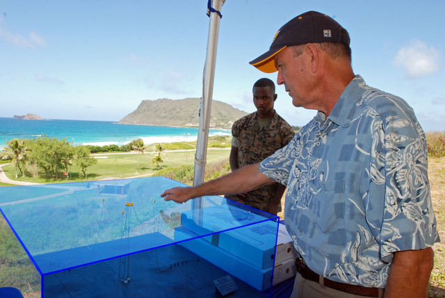 Patrick Cross, specialist at the Hawaii Natural Energy Institute at the University of Hawaii at Manoa, shows a model of a wave energy machine called the Lifesaver, a donut-shaped device that conve ...