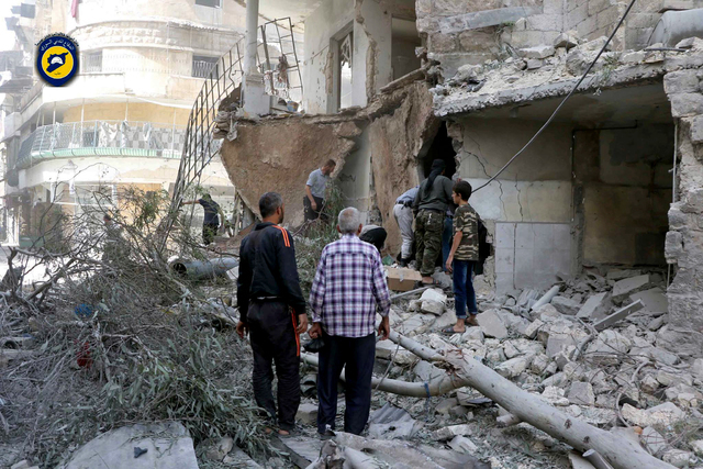 In this photo provided by the Syrian Civil Defense White Helmets, rescue workers work the site of airstrikes in al-Mashhad neighborhood in the rebel-held part of eastern Aleppo, Wednesday Sept. 21 ...