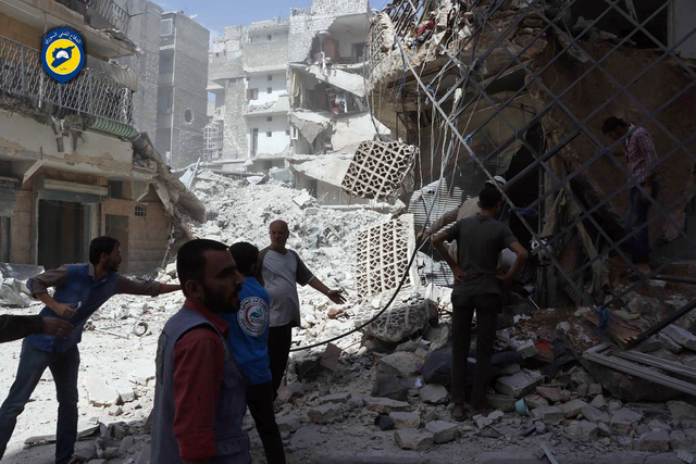 In this photo provided by the Syrian Civil Defense White Helmets, men stand amid rubble after airstrikes in al-Mashhad neighborhood in the rebel-held part of eastern Aleppo, Syria, Wednesday Sept. ...