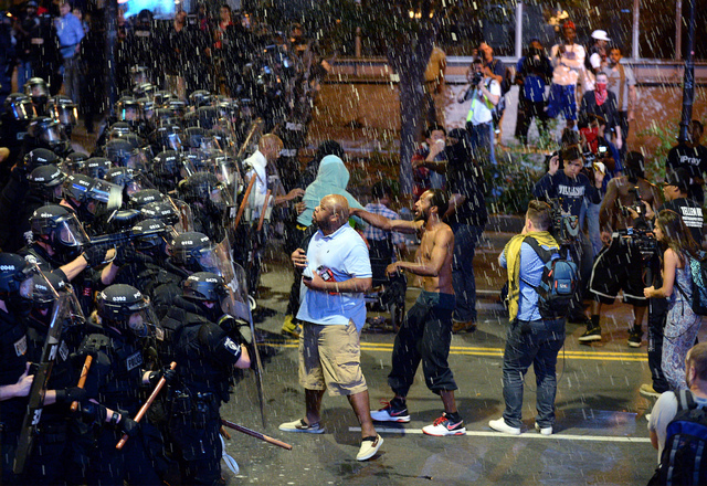 Debris falls upon Charlotte-Mecklenburg police officers and protesters as officers began to push protesters from the intersection near the Epicentre in Charlotte, N.C. Wednesday, Sept. 21, 2016. A ...