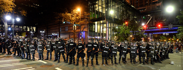 CMPD officers in riot gear block the intersection near the Epicentre in Charlotte, N.C. Wednesday, Sept. 21, 2016.  Authorities in Charlotte tried to quell public anger Wednesday after a police of ...